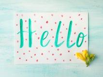 Hello uttrycker stavning vid blommor för guling för vattenfärghandbokstäver Royaltyfri Foto