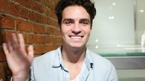 Hello vid stiligt sammanträde för ung man i vindinre, vinkande hand stock video