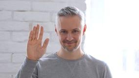 Hello vinkande hand för mellersta åldrig man Fotografering för Bildbyråer