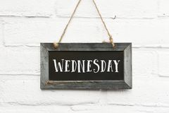 Hello wednesday text on hanging board white brick stones wall. Hello wednesday text on hanging blackboard white brick outdoor wall stock photos