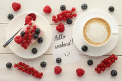Hello Weekend. Words on paper, cup of coffee and cake with fresh summer berries on white wooden table.  Summertime, enjoying weekend,  morning coffee, coffee Royalty Free Stock Photography