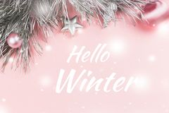 Hello winter greeting card with pastel pink Christmas background. Snow falling Royalty Free Stock Photo