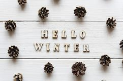 Hello winter greeting card. White wooden background with cones. And wooden letters Royalty Free Stock Photos