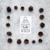 Hello winter hand lettering with hat icon. Winter pattern with pinecones on grey background top view Stock Photos