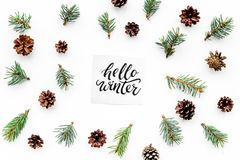 Hello winter hand lettering. Winter pattern with spruce branches and pinecones on white background top view Royalty Free Stock Image