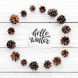 Hello winter hand lettering. Winter pattern with pinecones on white wooden background top view Royalty Free Stock Images