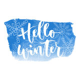 Hello winter hand written inscription. Hello winter white hand written inscription with snowflakes on blue watercolour banner background Royalty Free Stock Photo