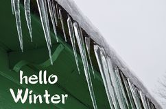 Hello Winter.Icicles on the roof of a green wooden house.Winter season concept. royalty free stock image
