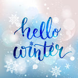 Hello winter text. Brush lettering at blue winter Stock Image