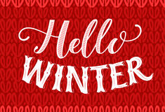 Hello winter text on red knitted texture. Vintage banner with hand lettering. Winter season vector retro card. Royalty Free Stock Photo