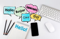 Hello word cloud in different languages of the world, background concept. Office desk table with computer, Smartphone and Notebook Royalty Free Stock Photography