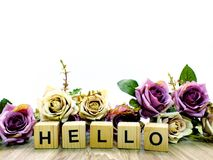 Hello word wooden block with artificial roses flowers decor. Ation on white background royalty free stock photography