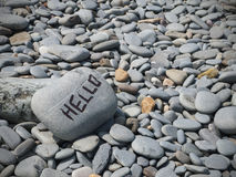 Hello writing on pebbled beach. Hello friendly writing on rock in Wales UK Royalty Free Stock Photo