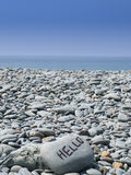 Hello writing on pebbled beach. Hello written on stone or use your own message Stock Photo