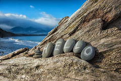 'hello' written in stones laying on driftwood. Stone laying on driftwood with words 'hello' written on them, shore and mountains behind. Washington State Stock Image
