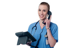 Hello, your appointment is confirmed. Happy female physician attending a phone call Stock Photography