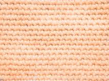Hellorangeer farbiger Strickpulli als Hintergrund Stockfotografie