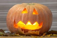 Helloween handmade pumpkin with leaves and light. Horror pumpkin royalty free stock photo