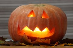 Helloween handmade pumpkin with leaves and candle light. Horror pumpkin royalty free stock photos