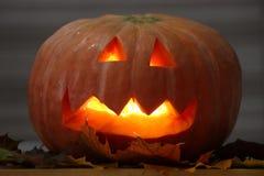 Helloween handmade pumpkin with leaves and candle light. Horror pumpkin stock photo