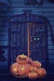 Helloween pumpkins. Heap of Helloween pumpkins near a haunted house wooden door Royalty Free Stock Photo