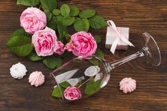 Hellrosa Rosen im Weinglas und -Präsentkarton auf dem hölzernen Hintergrund Lizenzfreies Stockfoto