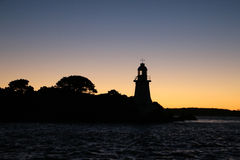 Hells gates lighthouse tasmania as silhouette in early morning sky Royalty Free Stock Image