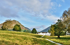Helm Crag viewed from Grasmere, on a summers day. A path winding its way through green fields, from Grasmere, towards Helm Crag, on a tranquil summers day in Royalty Free Stock Image