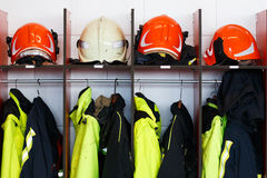 Helmen en brandkostuums in zijn kast worden geplaatst die Stock Foto