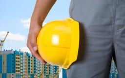 Helmet. Closeup  of yellow helmet at builder hands on building background Stock Photos