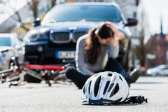 Helmet on the asphalt after accidental collision between bicycle and car royalty free stock image