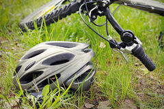 Helmet and bike on grass Royalty Free Stock Image