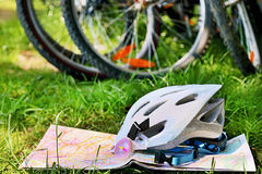Helmet, bikes, map, compass are on the grass background. Royalty Free Stock Photo