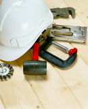 Helmet, clamp, stapler and other tools on wooden Stock Photography