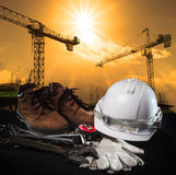 Helmet and construction equipment with building and crane agains Stock Image