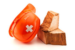 Helmet with court plaster and broken brick. Orange helmet with cross shaped court plaster and broken brick isolated on white royalty free stock photos