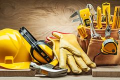 Helmet earphones hammer gloves and toolbelt with construction tools stock image