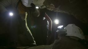 Helmet with flashlight in front of speleologists explores into the dark narrow cave. Close up stock video