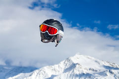 Helmet flying. Helmet with ski goggles flying on a background of mountains Royalty Free Stock Images