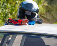 Helmet and gloves on a car rooftop Royalty Free Stock Photo