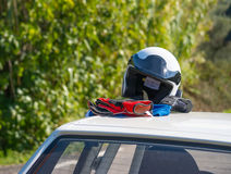 Helmet and gloves on a car rooftop Royalty Free Stock Image