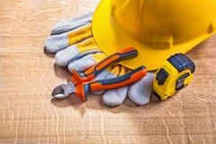 Helmet gloves nippers tapeline on wooden board Stock Photo