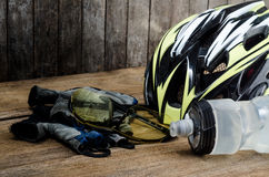 Helmet, gloves and water bottle - bicycle accessories on Wood. Stock Photo