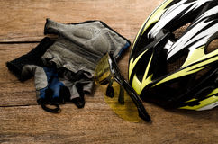 Helmet, gloves and water bottle - bicycle accessories on Wood. Royalty Free Stock Photography
