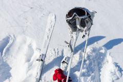 Helmet, Goggles, Poles and Skis on Snowy Hillside Stock Photos