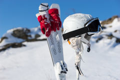 Helmet and Goggles with Skis and Poles on Hill Royalty Free Stock Photography