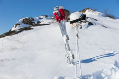 Helmet and Goggles with Skis and Poles on Hillside Royalty Free Stock Photo
