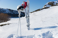 Helmet and Goggles with Skis and Poles on Hillside Stock Photo