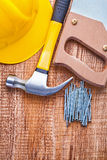 Helmet handsaw hammer and nails on old wooden Stock Photography