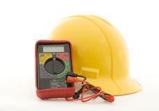 Helmet and multi-meter. A yellow hardhat and a multi-meter on a white background Royalty Free Stock Photo